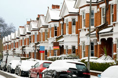 Winter Street in London. Snow covered Typical English Terraced Houses with SOLD and FOR SALE sign in London stock photo