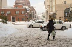Winter street scene walking on snow. People walking on snow covered the street during winter and heavy snow in Otaru, Hokkaido, Japan Stock Image