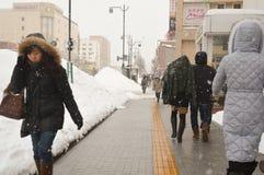 Winter street scene walking on snow. People walking on  snow covered the street during winter and heavy snow in Otaru, Hokkaido, Japan Stock Photo
