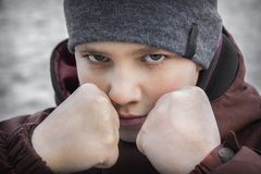 In winter, on the street, a serious boy stands protecting his face with his fists stock images