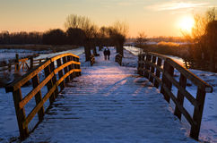 Winter stroll. Winter landscape at sunset in the Netherlands with two people taking a stroll in the evening stock photo