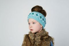 Winter style beautiful child model. Fashionable little girl in fur and knitted hat.winter style beautiful child model Stock Photography