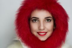 Winter style coat. Eskimo hood, bright red fur. Beautiful girl smiles with teeth white healthy clean tooth. Closeup portrait woman lady, professional make up Royalty Free Stock Image