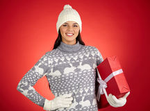 Winter style. Portrait of happy female with red giftbox looking at camera royalty free stock photo