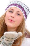 Winter style teenage girl sending a kiss to you. Isolated on white Stock Photography