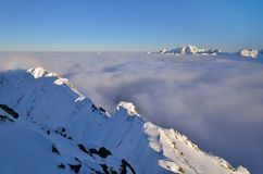 Winter summits over clouds. Knock-out view of snow-covered mountain peaks, in which the mountains seems to be floating above the clouds stock photos