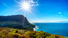 Winter sun casting its rays over the rugged coast and wind swept peaks near Cape Point. On the Cape Peninsula in South Africa under blue sky Royalty Free Stock Image