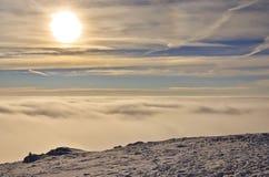 Winter sun in mountain. Sun in mountain over clouds stock photo