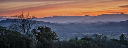 Winter Sunset over Sonoma Valley. The Winter Sun Sets over the Foggy and Misty Sonoma Valley with the Hills of the Sierra Nevada Mountain Range in the Distance Stock Photography