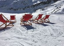 Winter sunbathing. Deck chairs in the snow Stock Photos