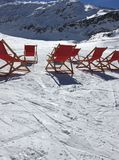 Winter sunbathing. Deck chairs in the snow Stock Photo