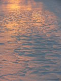 Winter: sunlit snow texture. Sculpted snow texture lit by sunset Stock Image