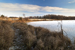 Winter Sunny day on the shore of a frozen lake stock photo