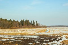 Winter sunny landscape, field forest and houses stock photos