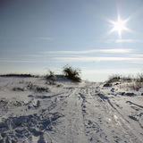 Winter Sunrise. Snowy winter landscape with clear blue sky and sun Stock Photo