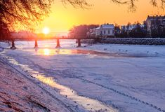 Winter sunrise on the bank of ice covered river Uz. Sun over the bridge of old European town Uzhgorod Royalty Free Stock Images