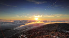 Winter sunrise. Beautiful sunrise above clouds in time lapse