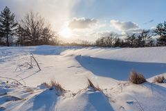 Winter Sunrise at Golf Course. A sandpit at a golf course covered in snow, and the sun setting in the distance. It is now called Acacia metropark Stock Image