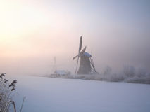 Winter sunrise in Holland. Sunrise in winter over a frozen canal and windmills at the famous dutch UNESCO site Kinderdijk, Holland stock images