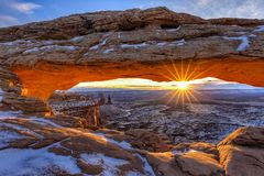 Winter Sunrise Mesa Arch. The winter sun rises on a cold January morning at Mesa Arch in Canyonlands National Park, Utah stock photos