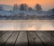 Winter sunrise over the river and empty wooden deck table. Royalty Free Stock Photo