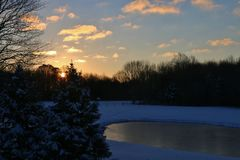 Winter sunrise over trees and lake Stock Photos