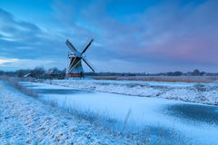 Winter sunrise over windmill in snow Royalty Free Stock Images
