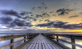 Winter sunrise on a pier. A winter sunrise on a wooden pier Royalty Free Stock Photos