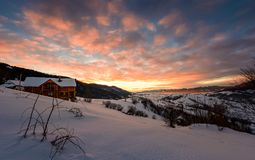 Winter sunrise with red clouds in the village. Beautiful winter countryside in mountains with snowy slopes Royalty Free Stock Photo