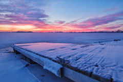 Winter Sunrise on a Snow covered Lake and Fishing Dock. Pink Clouds form over a Colorado Lake and the fishing dock on a very cold winter`s morning Stock Photos