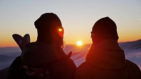 Winter Sunset Admire Couple Slowmotion. Slowmotion footage of a skier and snowboarder admiring a beautiful sunset stock video