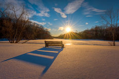 Winter sunset casting a bench shadow in the snow. A winter sunset casts a shadow of a bench on the untouched snow in New Jersey Royalty Free Stock Images
