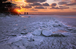 Winter sunset on the frozen lake in broken ice Royalty Free Stock Image