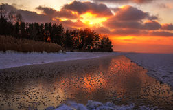 Winter sunset on a frozen lake with a reflection on the ice. Stock Images