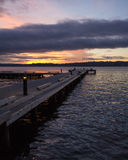 A diagonal view of a pier on a lake in a winter sunset at Waverly Beach Park, Washington, with Seattle skyline in the background Royalty Free Stock Photos