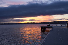A partial view of a pier on a lake in a winter sunset at Waverly Beach Park, Kirkland, Washington. With Seattle skyline in the background stock photo