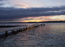 A diagonal view of a pier on a lake in a winter sunset at Waverly Beach Park, Kirkland, Washington. With Seattle skyline in the background Royalty Free Stock Photos