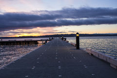 Straight view of a pier on a lake in a winter sunset at Waverly Beach Park, Kirkland, Washington. A straight view of a pier on a lake in a winter sunset at royalty free stock images