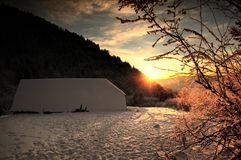 Winter sunset. The sunset on the hills of Romania, in winter. Some snowy branches and a house roof, completely covered by snow are part of the landscape Stock Images