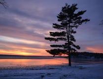 Winter sunset on the horizon across Minnesota lake. Orange yellow colors of wintertime vacationland sunset in Minnesota Stock Photos