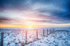 Winter sunset on the lake with fence posts stock photography