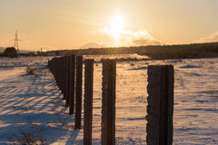 Winter sunset landscape snow covered country fence field. Royalty Free Stock Photo