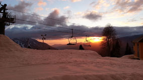 Winter sunset in the mountains. Ski resort in Krasnaya Polyana, peaks and clouds, snow and cableway. Travel Russia, Sochi Stock Photos