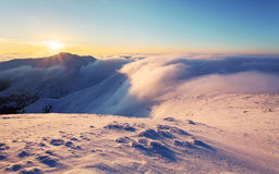 Winter sunset over the clouds with sun. Stock Photo