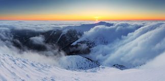 Winter sunset over the clouds with sun. Royalty Free Stock Image