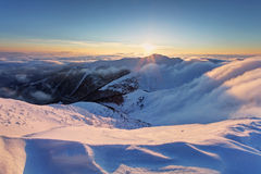 Winter sunset over the clouds with sun. Stock Image