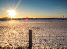 Winter Sunset Over A country Farm. Winter Sunset with snow covered farm field Royalty Free Stock Photos