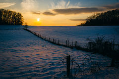 Winter sunset over a fence and snow covered farm field in rural Stock Photos