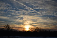 Winter sunset over field with wispy clouds. Royalty Free Stock Image