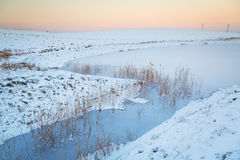 Winter sunset over frozen pond Royalty Free Stock Image